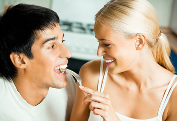 Young happy couple eating salad