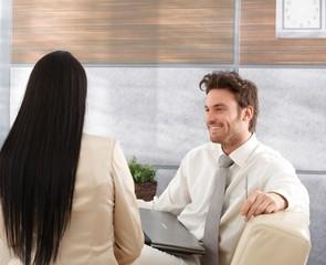 Smiling businessman talking to woman
