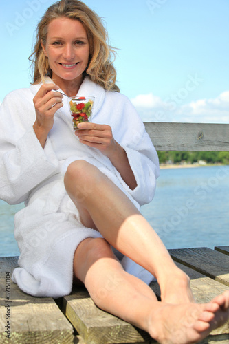 woman eating fruit cocktail and sitting by the water