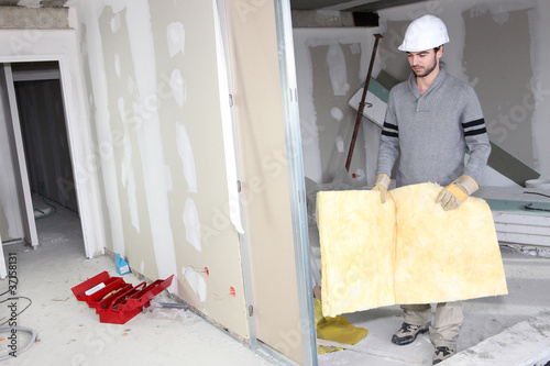 Builder carrying wall insulation