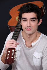 young man holding a guitar on his shoulder