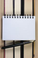 Bloc de notas y pluma estilográfica con libros