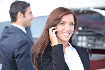 businesswoman on the phone and businessman in the background