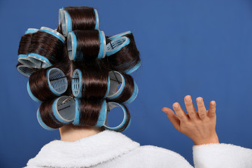 Back view of a woman wearing rollers and waving