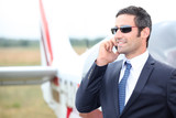 Executive standing in front of his private plane
