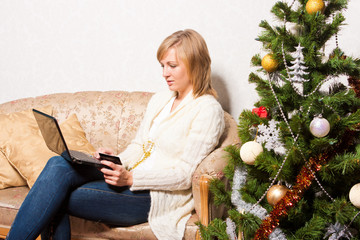 young woman sits with a notebook near Christmas tree
