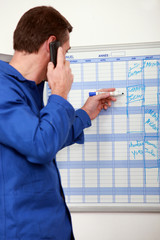 Manual worker writing names onto a wall planner