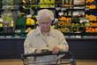 Seniorin liest Nährwerteangaben von Lebensmitteln im Supermarkt