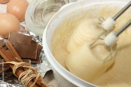 Cake ingredients in bowl with electric mixer next to it