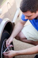 Young man checking tire pressure