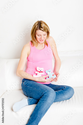 Beautiful pregnant woman sitting on white  sofa