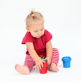 Cute toddler girl playing with painting colors
