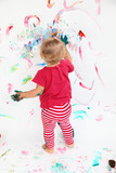 Little toddler girl painting with colors on white wall