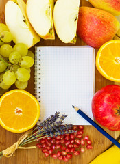 blank notebook for recipes with colorful fruits