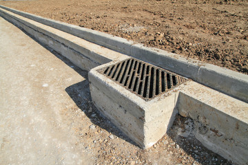Concrete curb and drainage well at road construction site.
