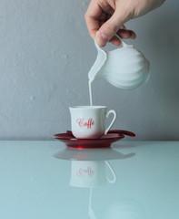 Versare il latte nella tazzina del caffè