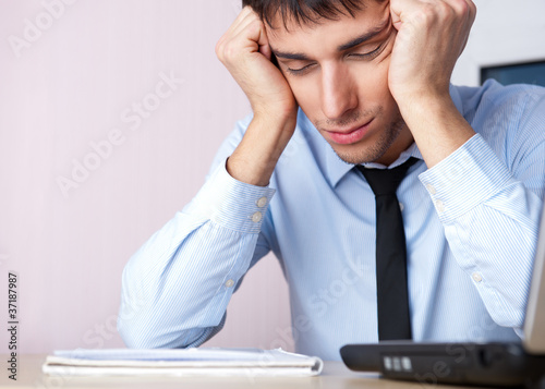 Tired businessman sleeping at his desk in the office with both a