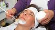 Kosmetikerin trägt mit Pinsel Gesichtsmaske auf