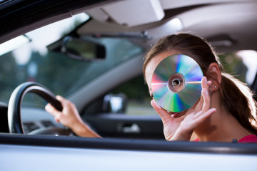 Young female driver playing music in the car