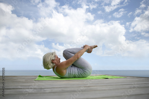 senior woman making exercises on the beach