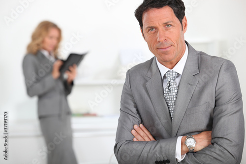 Smart businessman with a female colleague in the background