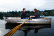 Couple in love riding a romantic rowboat on a quiet lake