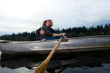 Happy couple in love rowing a small boat on a quiet lake