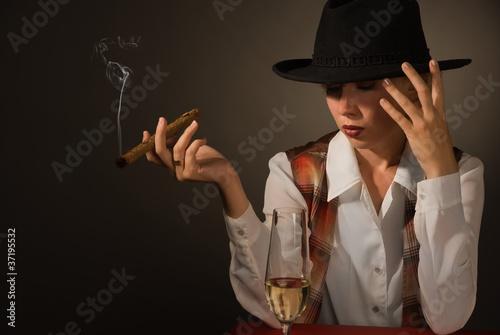 Leinwandbild Motiv Beautiful woman in a black hat with a cigar
