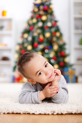 Cute boy laying in front of christmas tree