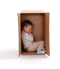 Sad little boy hiding in cardboard box
