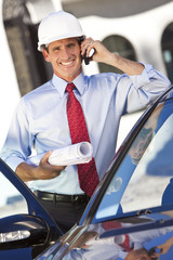 Businessman Architect In Hard Hat On Cell Phone By Car