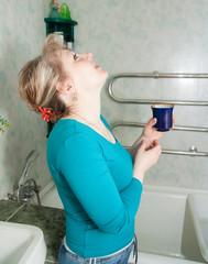 woman with glass of  medicine gargling