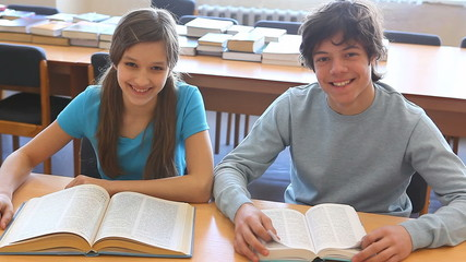 Pupils reading textbooks then looking at camera