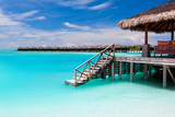 Over water bungalow with steps into blue lagoon - Fine Art prints