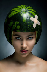 Attractive girl with watermelon as a helmet
