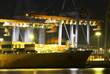 Large container ship in a busy dock at night