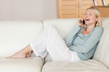 Woman enjoying phone call on the sofa