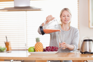 Woman pouring self made juice into a glass