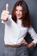 Portrait of a beautiful young business woman standing and thumbs