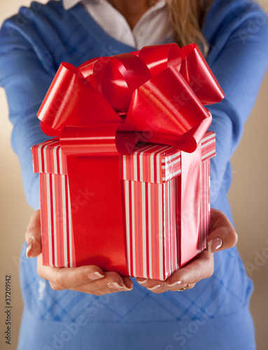 Casually dressed female holding nicely wrapped present.