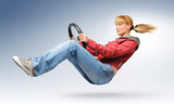 Young girl car driver in red jacket with a wheel, concept