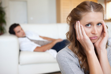 Woman suffering from headache with man on the sofa behind her
