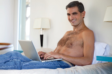 Shirtless Man Working on Laptop