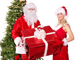 Santa claus and  girl holding gift box by christmas tree..