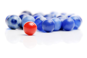 One vintage red marble standing out from blue marbles