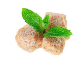 Three brown lump cane sugar cubes with peppermint leaves, isolat