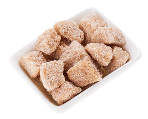 Brown lump cane sugar in a rectangular sugar-basin, isolated on