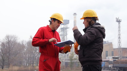 Supervisor and worker in factory, control work
