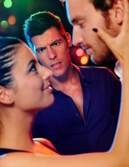 Desperate man looking at flirting couple in disco