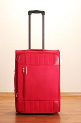 Red suitcase isolated in the room